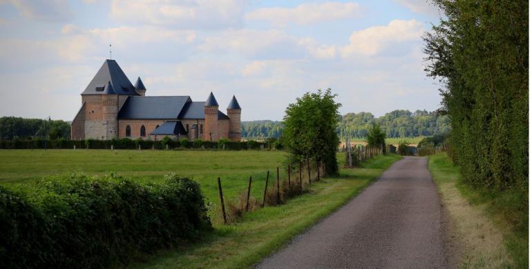 église fortifiée de thiérache au bout d'un chemin